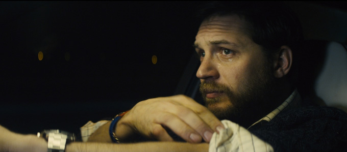 Tom Hardy still sits in a car.