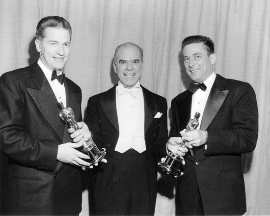 "Elmo Williams (L)and Harry Gerstad (R)< receiving the Academy Award in Editing for ""High Noon"", from Frank Capra (C)."