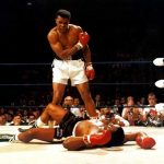 Muhammad Ali knocks down his opponent in the ring.
