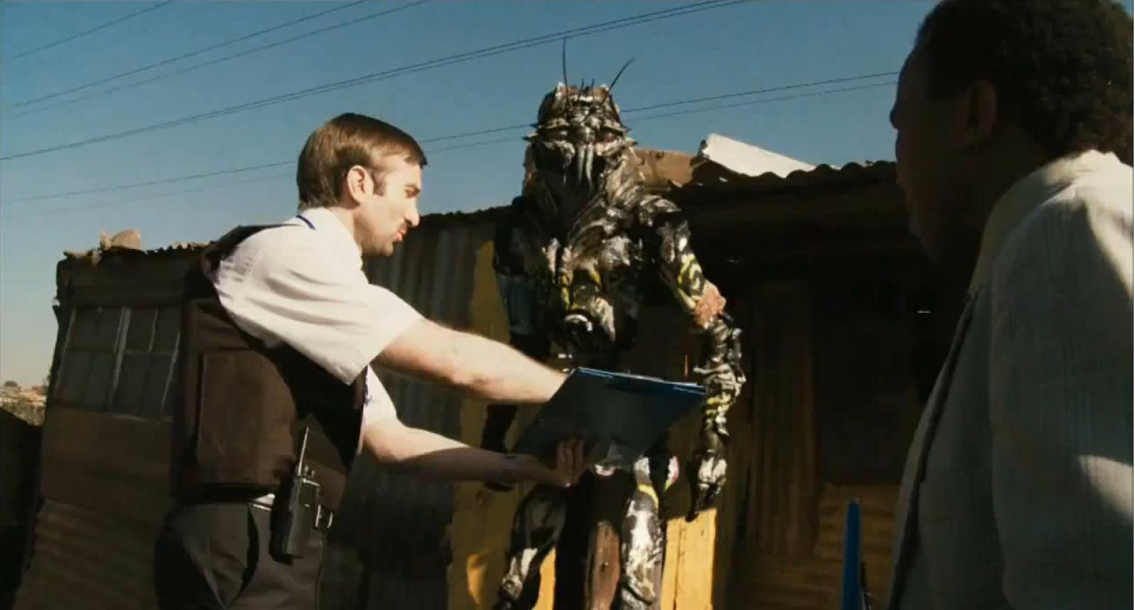 Wikus (Sharlto Copley) explains to one of the aliens that it's time to go.