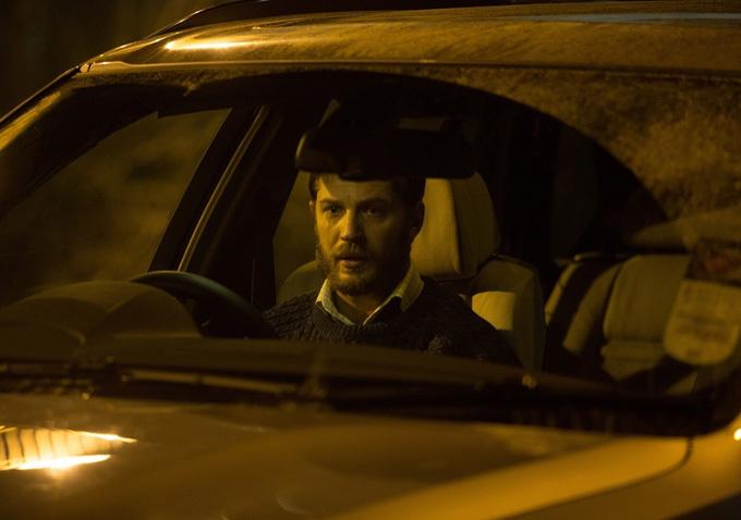 Tom Hardy sits in a car.