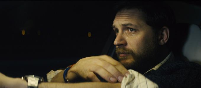 Tom Hardy still sits in a car.