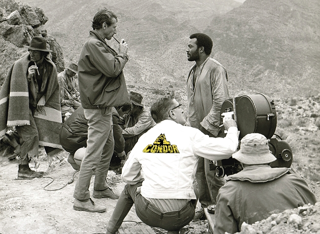 "John Guillerman (L, smoking pipe) talks with actor Jim Brown (R), on the set of ""El Condor"" (1970)."