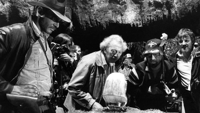 Harrison Ford (L), Douglas Slocombe (C), and Steven Spielberg (CR) and Lawrence Kasdan (R) on the set of Raiders of the Lost Ark (1981).